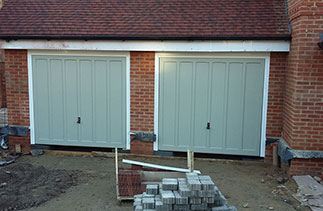 Two Woodrite timber Churchill style up and over garage doors fully finished in a colour match to Farrow & Ball French Grey. Fitted to plot 3 in Hartley Wintney, Hampshire.