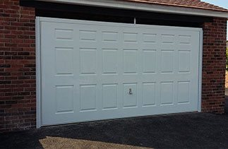 A Wessex 3 Crown Gloss white Georgian style purpose made up and over garage door with a white steel frame and a white chassis. The door is fitted with a Garador Chrome handle. Fitted in Berkshire.