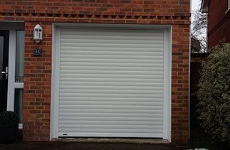 A White Seceuroglide Excel roller shutter garage door fitted behind the lintel and within the brick work. Complete with White upvc on the brick faces. Fitted in Reading, Berkshire.